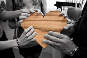 Photo Via: www.Pexles.com, community members join together and hold a heart crafted from wood.