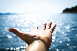 Photo Via: www.Pexles.com, helping hand reaching out towards the sun across a large body of water.